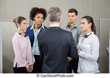 Manager Discussing With Serious Employees