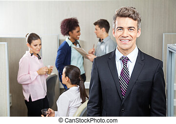 Happy Manager With Employees Discussing In Background -...
