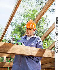 Construction Worker Using Electric Saw - Male construction...