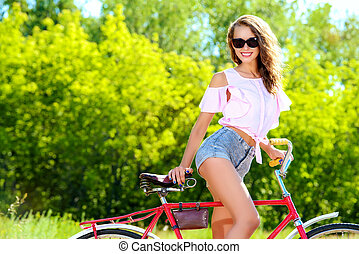 walk on the bike - Happy girl riding a bicycle in the park...