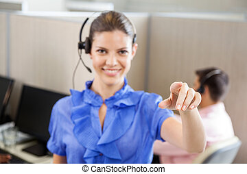 Smiling Call Center Employee Pointing In Office - Portrait...