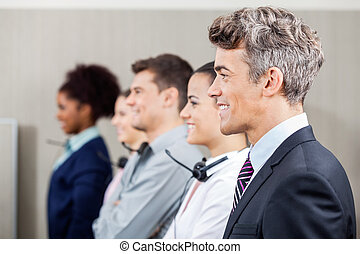 Happy Manager Standing In Row With Call Center Employees -...