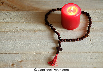 Cross and candle - Rosary with a cross and a candle on a...