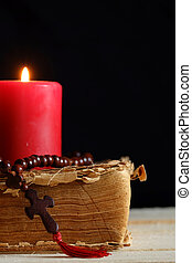 Cross and candle - Rosary with a cross, old Bible and a...