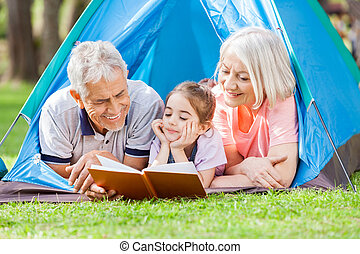 Grandparent With Granddaughter Reading Book At Campsite