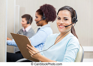 Smiling Female Customer Service Representative Writing On...