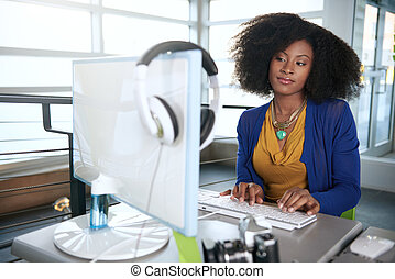 Portrait of a smiling woman with an afro at the computer in...