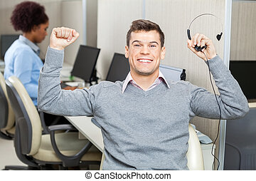 Customer Service Representative With Arms Raised Holding...
