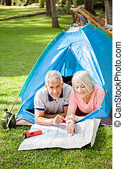 Senior Couple Studying Map At Campsite In Park - Portrait of...