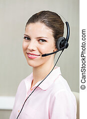 Smiling Female Call Center Employee Using Headphones -...
