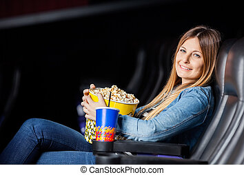 Smiling Woman With Snacks At Movie Theater - Side view...
