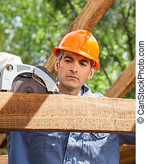 Construction Worker Using Electric Saw On Timber Frame -...