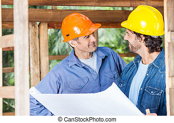 Smiling Architects Discussing Over Blueprint At Site