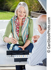Happy Senior Woman Playing Rummy With Man