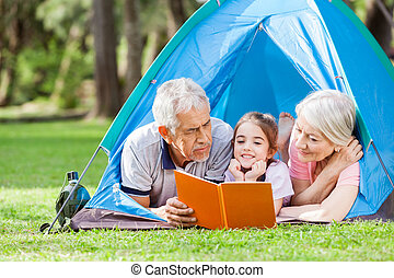 Grandparents With Granddaughter Reading Book In Tent
