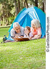 Grandparents Reading Book For Granddaughter At Campsite