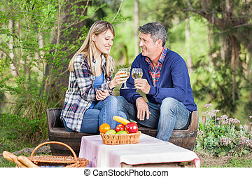 Smiling Couple Toasting Wine Glasses At Campsite - Smiling...