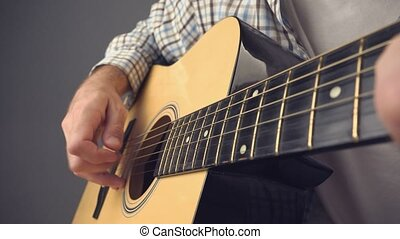 Man playing rock tune chords on acoustic guitar, unplugged...