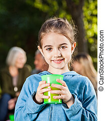 Girl Holding Glass Of Juice At Campsite