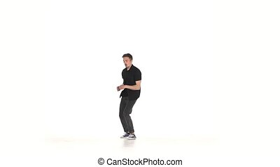 Young, stylish b-boy man in shirt doing brake dancing movements, on white, slow motion