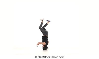 Modern dancer dancing brake-dance on head, white, slow...