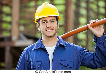 Happy Construction Worker Holding Pipe - Portrait of happy...