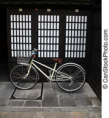 A simple bicycle outside a traditional style japanese doorway in Takayama - Japan