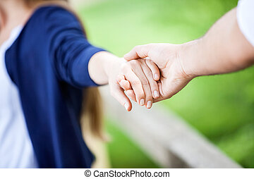Couple Holding Hands In Park - Cropped image of young couple...