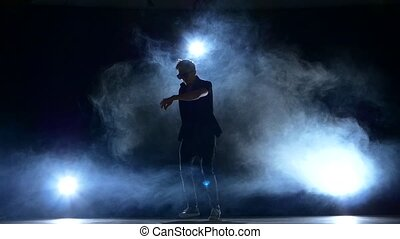 Young hiphop dancer making a move, smoke, silhouette, slow...