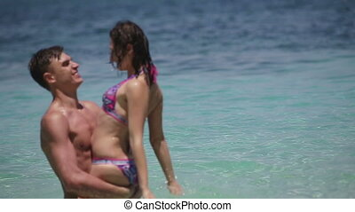 Couple splashing water. - The young man holds the girl on...