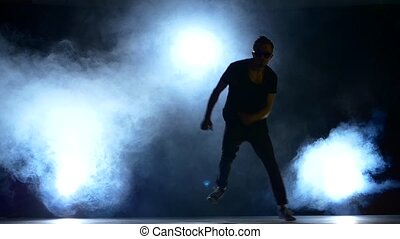Young hiphop dancer making a move, jump, smoke, silhouette,...