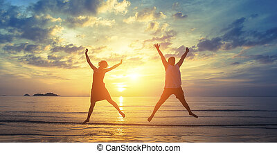 couple jumping on the ocean beach - Silhouettes of happy...