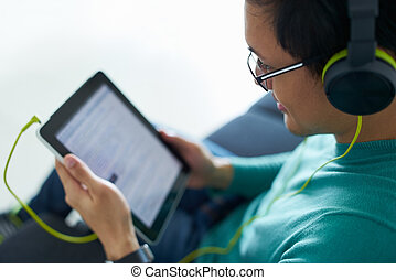 Chinese Man With Green Headphones Listens Podcast Tablet PC...