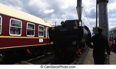 Loading steam locomotive with water at railway station -...