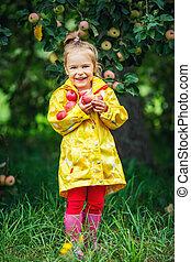 Little girl in the apple garden - Happy little girl holding...
