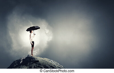 It is crisis time - Young businesswoman with black umbrella...