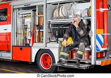 Fireman Drinking Coffee While Sitting In Truck - Full length...