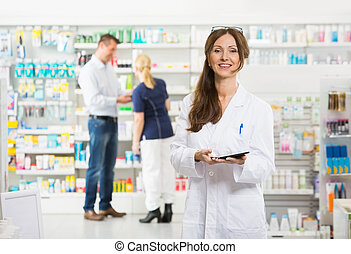 Smiling Female Chemist Holding Digital Tablet At Pharmacy -...