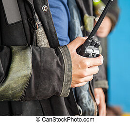 Firefighter Holding Walkie Talkie - Midsection of...