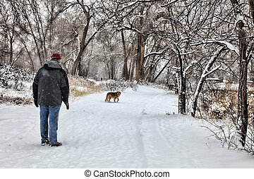 Man and Dog on Snowy Walk - Mature man and his dog walk down...