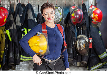 Happy Firewoman Holding Helmet At Fire Station - Portrait of...