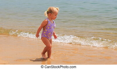 two little girls with hairtails play in shallow seawater -...