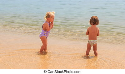 two little girls with hairtails play with wave in seawater -...