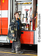 Smiling Firefighter Standing By Truck At Fire Station
