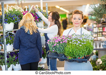 Florist Carrying Flower Plants With Colleague Assisting Customer
