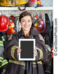 Firewoman Showing Digital Tablet At Fire Station - Portrait...