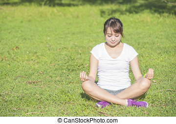 Young girls do yoga in the park