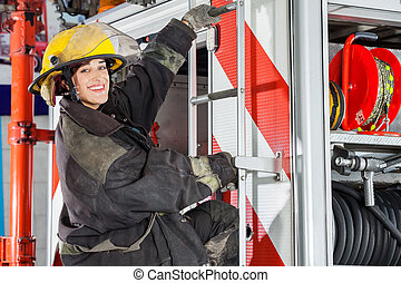 Smiling Firefighter Standing On Truck At Fire Station - Side...