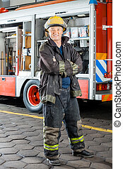 Happy Fireman Standing Against Truck - Portrait of happy...