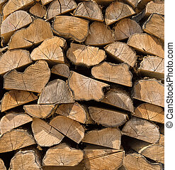 Woodpile with brown, half cut smaller tree trunks in...